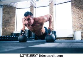 Muscular man doing push ups in gym
