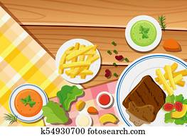 Table scene with fries and steak on the dish