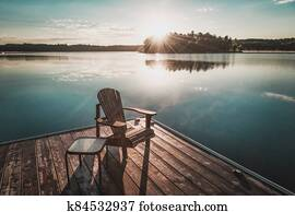 Muskoka chairs sitting on a wood dock facing a calm lake. Across the water is a white cottage nestled among green trees. There is a boat dock on the water in front of the cottage.