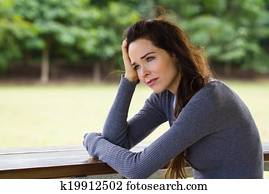 Sad depressed woman sitting outdoors