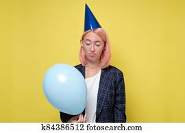 woman in birthday cap with noisemaker. Girl does not want to celebrate her birthday.