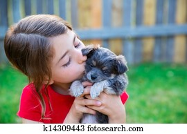 children girl kissing her puppy chihuahua doggy
