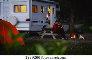 Couple sitting by campfire