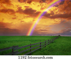 Rainbow in country field with gold clouds